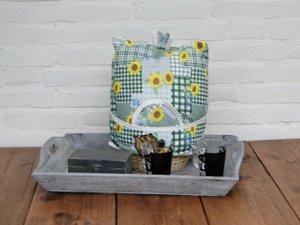 Theemuts met mandje: gele bloemen op groen patroon